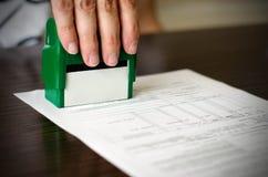 Stämpel för trycka på för hand rubber på dokument Royaltyfri Foto