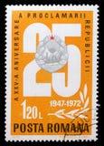 Stämpel som skrivs ut av Rumänien, shower 25 och det nationella emblemet, årsdag 25 av republikfrågan Royaltyfri Foto