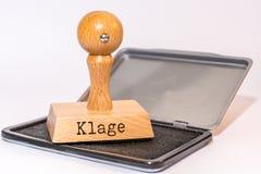 Stämpeldyna och stämpel med det tyska ordet 'dräkt ', arkivbild