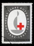 Stämpeln som skrivs ut i österrikaren, är hängiven till den 100. årsdagen av det internationella Röda korset Arkivbild