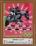 Stämpeln som skrivs ut i Arabrepubliken Jemen, visar hästkapplöpning, OS:er i Munich Royaltyfria Bilder