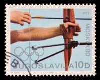 Stämpeln som skrivs ut i Jugoslavien, visar bågskyttekonkurrens, olympiska spel i Moskva Arkivbilder