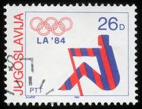 Stämpeln som skrivs ut i Jugoslavien, visar olympiska spel i Los Angeles Arkivbilder