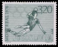 Stämpeln som skrivs ut i Jugoslavien, visar olympiska spel i Montreal Royaltyfria Foton