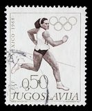 Stämpeln som skrivs ut i Jugoslavien, visar spring, olympiska spel i Mexico - stad Arkivbilder