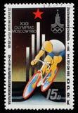 Stämpeln som skrivs ut i Nordkorea, shower cyklar lopp, emblem av XXII OS royaltyfri foto