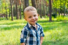 Stände des kleinen Jungen und Lächeln im Park an einem sonnigen Tag Lizenzfreie Stockbilder