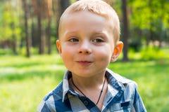 Stände des kleinen Jungen und Lächeln im Park an einem sonnigen Tag Lizenzfreie Stockfotografie