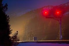 Stände eines Eisenbahnsignals schützen, während ein Zug sich nähert Lizenzfreies Stockfoto