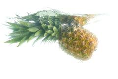 stäng fallande ananas upp vatten arkivbild