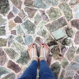 Stäng sig av Bare fot med rött spikar upp i sandaler och jeanskvinna på tegelplattabakgrunden Arkivfoto
