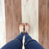 Stäng sig av Bare fot med rött spikar upp i sandaler och jeanskvinna på tegelplattabakgrunden Arkivfoton