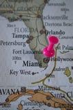 Stäng sig av det Hollywood stiftet pekade upp på världskartan med en rosa häftstift royaltyfri bild