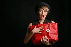 Stäng sig av en härlig kvinna med en bra avkänning av blidkar upp och att rymma hennes utsmyckade röda påse royaltyfria foton
