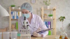 St?ng sig av en kvinnlig laborant f?r och antecknar upp studien genom att anv?nda ett mikroskop stock video
