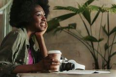 Stäng sig av gladlynta unga afrikanska kvinnan som den har, vilar upp i kafeteria arkivfoto