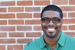 Stäng sig upp att le bärande glasögon för den unga svarta mannen som ser kameran mot bakgrund för tegelstenvägg med kopieringsutr Arkivfoto