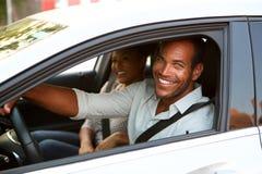 Stäng sig upp att le mannen och kvinnan i bil på vägtur royaltyfri foto
