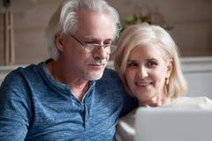 Stäng sig upp av åldrig make, och frun kopplar av med bärbara datorn royaltyfria bilder