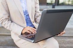 Stäng sig upp av affärskvinna med bärbara datorn i stad Arkivbilder