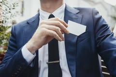 Stäng sig upp av affärsmannen som sätter det tomma affärskortet i hans fack för det blåa omslaget royaltyfria bilder