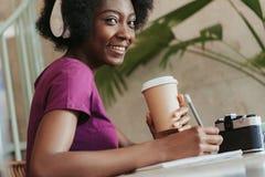 Stäng sig upp av afrikansk kvinna med lockigt hår som håller cupholderen i armar royaltyfria bilder