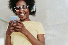 Stäng sig upp av afrikanskt bära för dam som är tillfälligt, och att hålla mobiltelefonen i armar arkivfoton