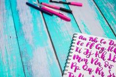 Stäng sig upp av anteckningsboken med för abc-alfabetet för handen utdragna bokstäver och färgrika pennor på blå träskrivbordbakg royaltyfri bild