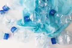 Stäng sig upp av använda plast- flaskor och racka ner på påsen Royaltyfri Foto