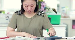 Stäng sig upp av asiatiska kvinnliga revisor- eller bankirdanandeberäkningar stock video