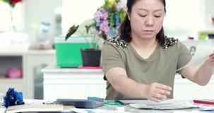 Stäng sig upp av asiatiska kvinnliga revisor- eller bankirdanandeberäkningar lager videofilmer