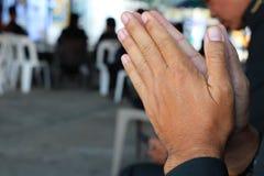 Stäng sig upp av asiatiska manliga händer som tillber enligt buddistiska troar royaltyfria foton
