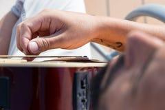 Stäng sig upp av assistenten av en gitarrist som spelar aningar arkivfoto