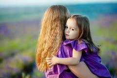 Stäng sig upp av att älska modern och behandla som ett barn att posera i blomningfält Royaltyfri Bild