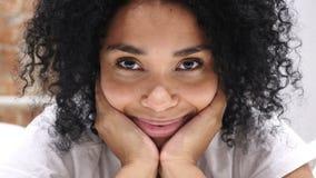 Stäng sig upp av att blinka ögon av afro--amerikanen kvinnan som ligger i säng stock video