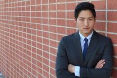 Stäng sig upp av att le den enkla unga manliga chefen i blått omslag, skjorta och slips med kopieringsutrymme och hans korsade ar Arkivfoto