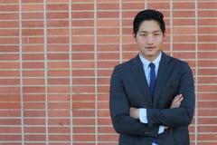 Stäng sig upp av att le den enkla unga manliga chefen i blått omslag, skjorta och slips med kopieringsutrymme och hans korsade ar Royaltyfri Foto