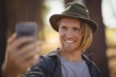 Stäng sig upp av att le den unga mannen som klickar selfie Arkivfoton