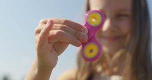 Stäng sig upp av att le flickan som spelar med spinnaren i fältet på Sunny Day stock video