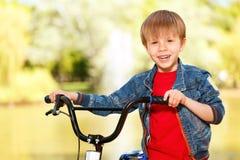 Stäng sig upp av att le pojken som står nära cykeln Arkivfoto
