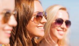 Stäng sig upp av att le unga kvinnor i solglasögon royaltyfria bilder