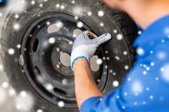 Stäng sig upp av auto mekaniker med bilgummihjulet Royaltyfri Foto