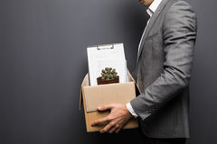 Stäng sig upp av avfyrat mananställdnederlag bak asken med personliga objekt på grå bakgrund royaltyfri foto