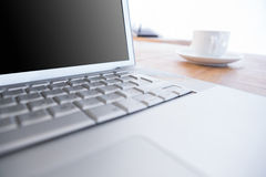 Stäng sig upp av bärbara datorn och kaffe på ett skrivbord Royaltyfri Bild