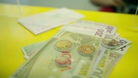 Stäng sig upp av bankiren som ut betalar europengar och bekräftar med stämpeln arkivfilmer
