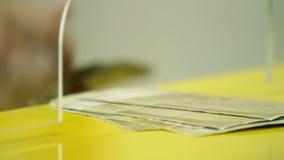 Stäng sig upp av bankiren som ut betalar europengar till och med bankfönster stock video