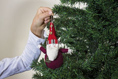 Stäng sig upp av barnet som hänger den dekorativa Santa Claus leksaken på julgranen royaltyfria bilder