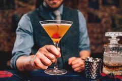 Stäng sig upp av bartendern som tjänar som den manhattan coctailen i martini exponeringsglas royaltyfri foto