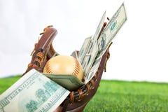 Stäng sig upp av baseball i en handske med dollarräkningar i begrepp av Royaltyfria Foton