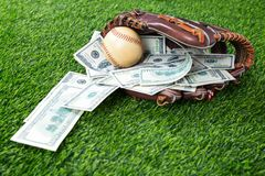 Stäng sig upp av baseball i en handske med dollarräkningar i begrepp av Fotografering för Bildbyråer